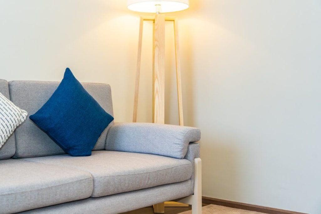 Sofa mit einer Stehlampe und Kissen