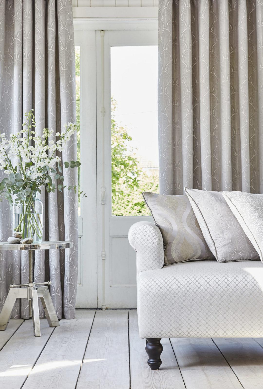 Sofa mit Gardienen und einer Pflanze auf einem Tisch