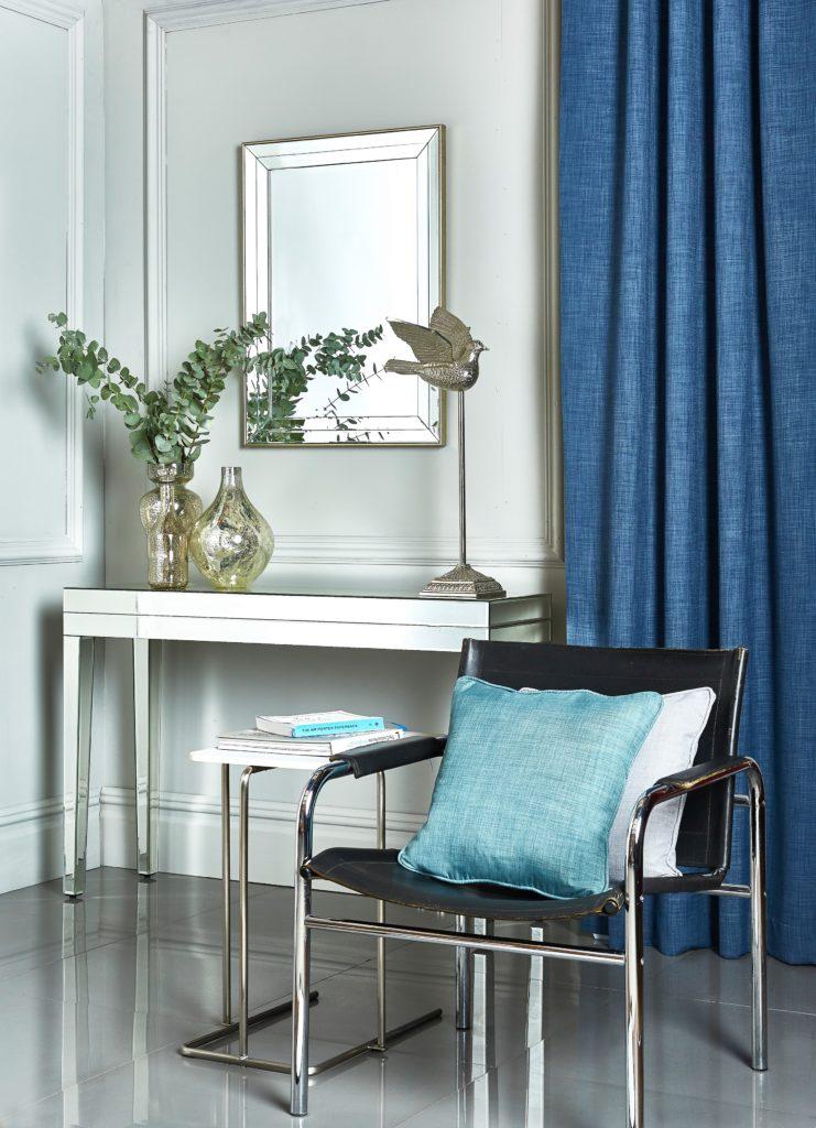 Blaue Gardinen mit einem Stuhl und einer Konsole mit Blumen